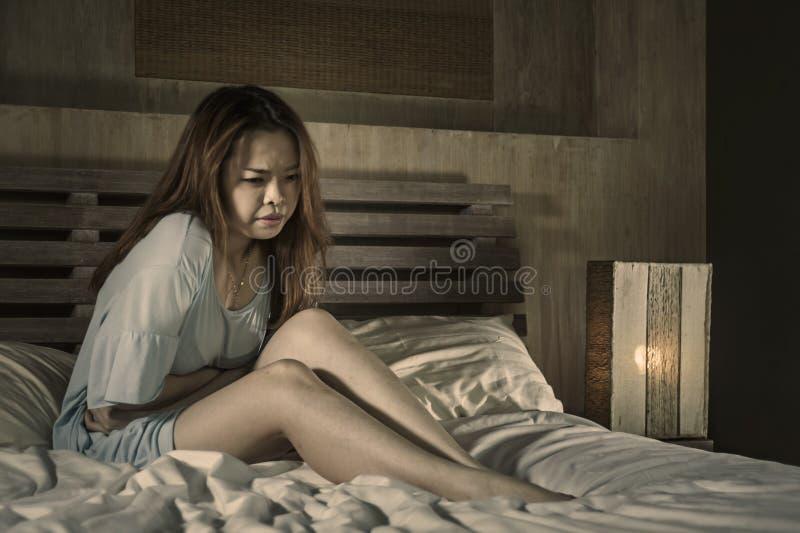 Het gedeprimeerde mooie Aziatische Koreaanse meisje die menstruatie en periode aan pijn lijden die ziek in bed bij nacht met maag stock afbeeldingen