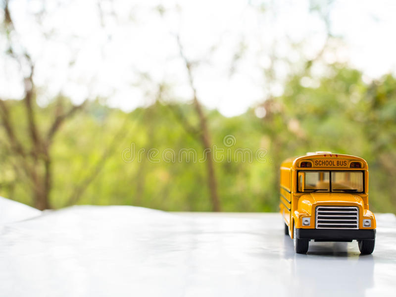 Het geel plastiek van de schoolbus en metaalstuk speelgoed model op het land roa stock fotografie