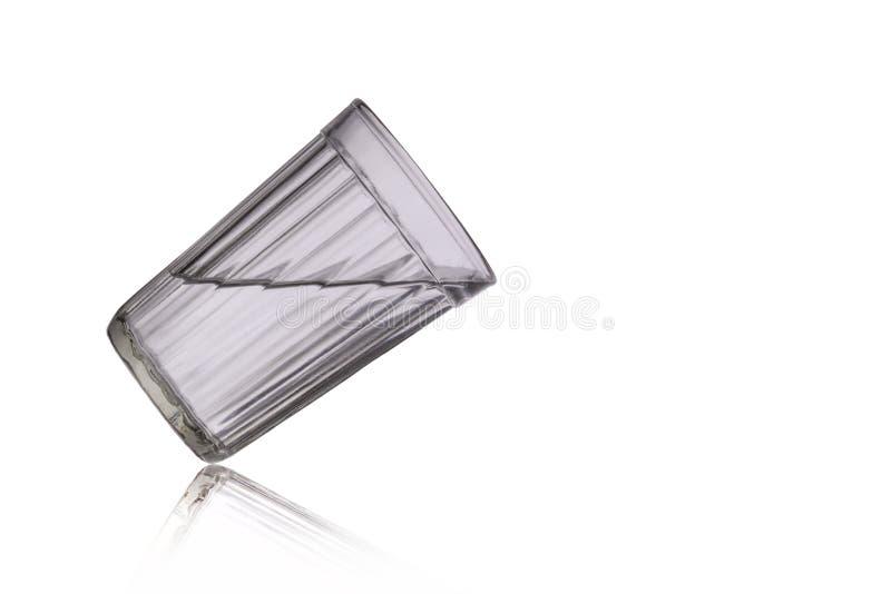 Het gefacetteerde glas met een drank is overgeheld stock fotografie