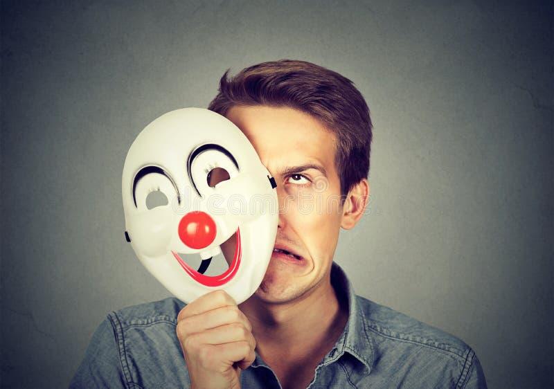 Het gefrustreerde boze mens verbergen achter gelukkig gezicht stock afbeelding