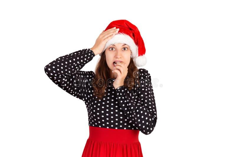 Het gefrustreerde wijfje voelt bezorgd en verrast en bijt vingerspijkers in verwarring het emotionele meisje in Kerstmishoed van  royalty-vrije stock foto's