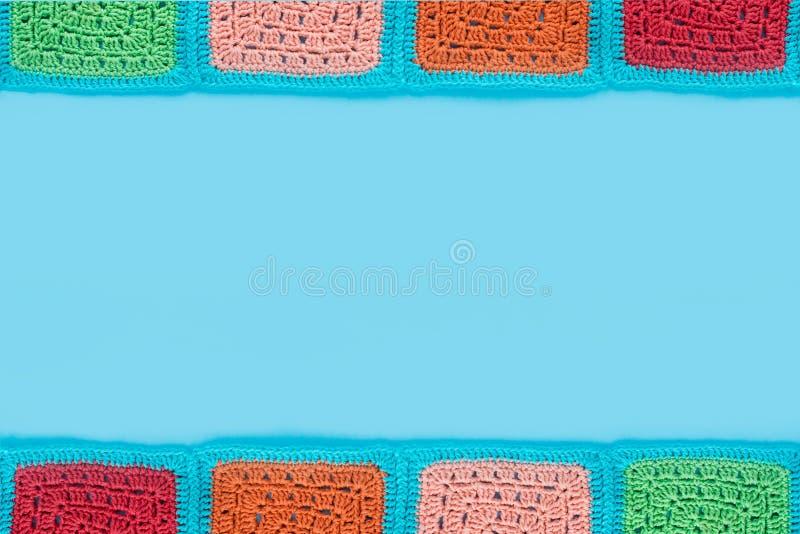 het gehaakte kanttafelkleed van multicolored vierkanten siert op een bluachtergrond, hoogste mening, plaats voor tekst, natuurlij stock fotografie