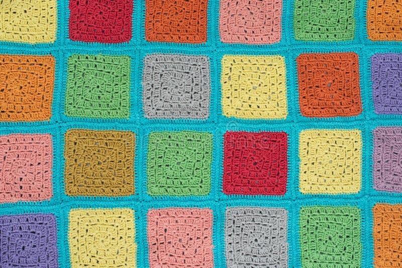 het gehaakte kanttafelkleed van multicolored vierkanten siert op een grijze achtergrond, hoogste mening, plaats voor tekst, natuu royalty-vrije stock fotografie