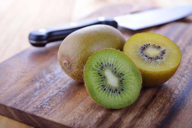 Het geheel en het heft snijden aan boord groene en gouden kiwi royalty-vrije stock foto's