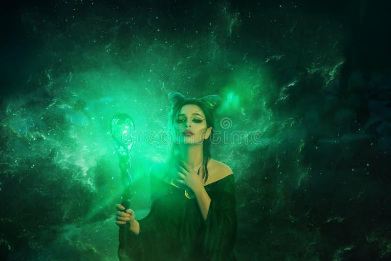 Het geheimzinnige donkere elf kreeg vreselijke vloek, die meisje met hoornen op hoofd en gloeiende fonkelende magische stok in ha royalty-vrije stock foto