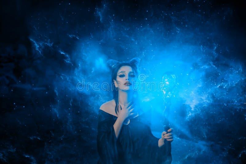 Het geheimzinnige donkere elf kreeg vreselijke vloek, die meisje met hoornen op hoofd en gloeiende fonkelende magische stok in ha stock foto