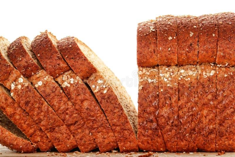 Het gehele Brood van het Brood van de Tarwe dat in Plak op Houten Raad wordt gesneden stock fotografie