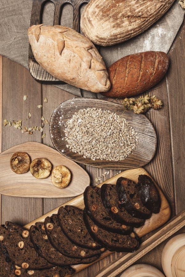 Het gehele korrel multigrain brood, geheel en gesneden die, bevat zaden op zwarte worden geïsoleerd royalty-vrije stock foto