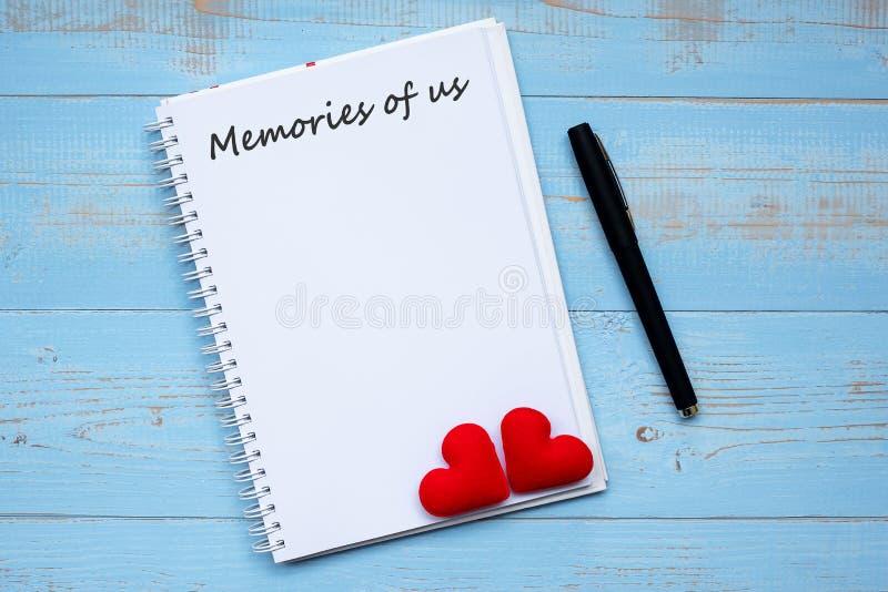 Het GEHEUGEN VAN het woord van de V.S. op notitieboekje en pen met paar rood hart vormt decoratie op blauwe houten lijstachtergro royalty-vrije stock fotografie