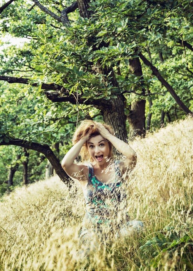 Het gekke jonge Kaukasische brunette houdt haar in aard stock foto