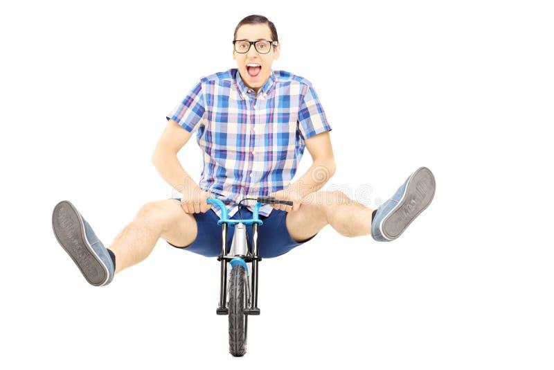 Het gekke jonge mens stellen op een kleine fiets royalty-vrije stock foto