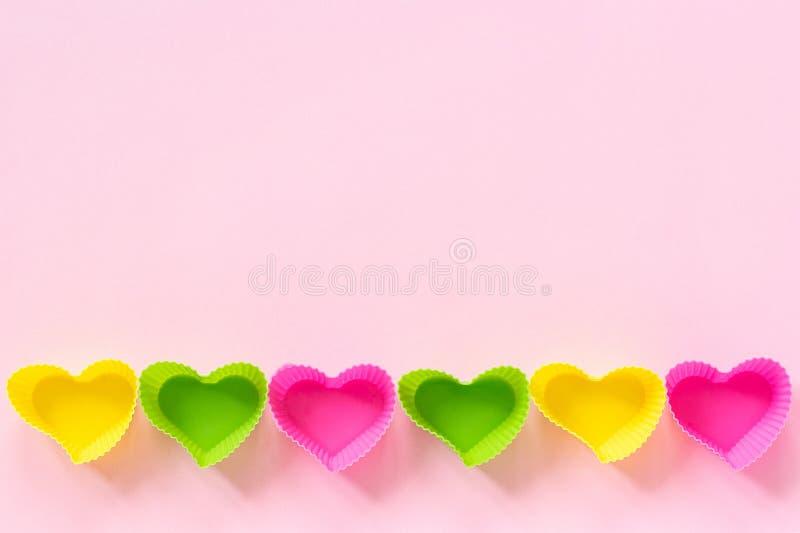 Het gekleurde die siliconehart vormde vormenschotel voor baksel cupcakes in rij onderste rand wordt gevoerd op roze document acht royalty-vrije stock foto