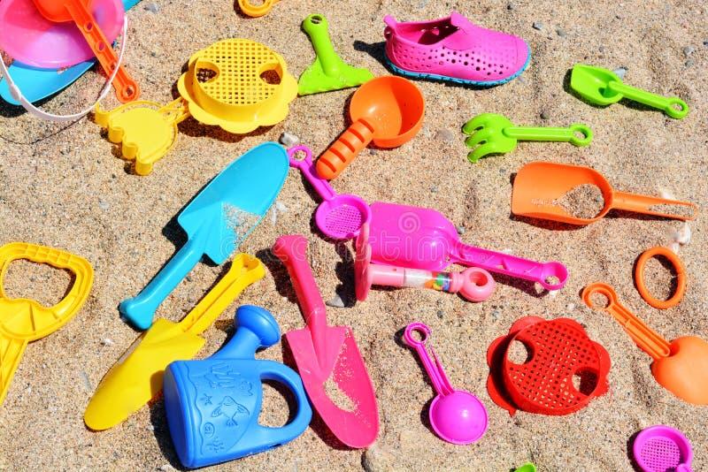 Het gekleurde strandspeelgoed op zandachtergrond, jonge geitjes heeft pret bij de kust stock foto