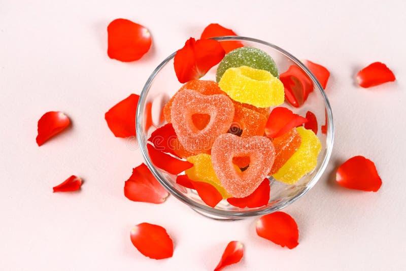 Het gekleurde suikergoed met twee rode harten in glaskom en nam bloemblaadjes toe stock foto