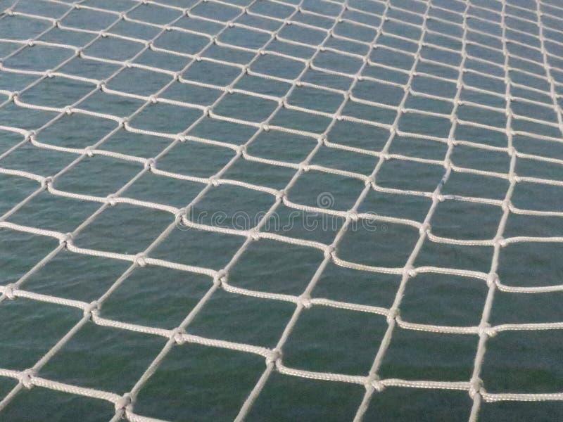 Het geknoopte visnet hangen boven het water in de haven van Scheveningen Nederland royalty-vrije stock foto