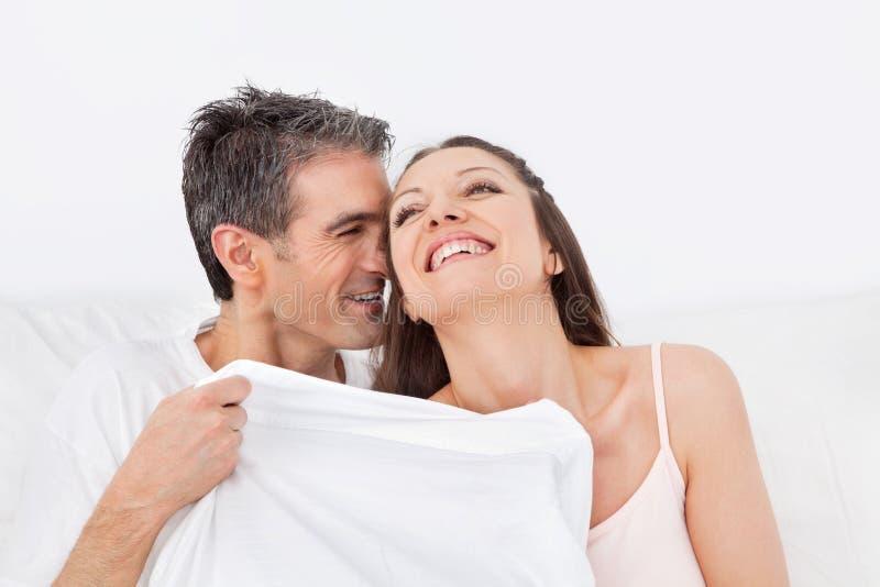 Het geknuffel van de man en van de vrouw in bed stock fotografie