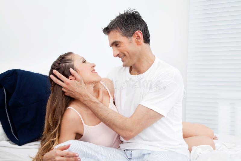 Het geknuffel van het echtpaar in bed stock foto