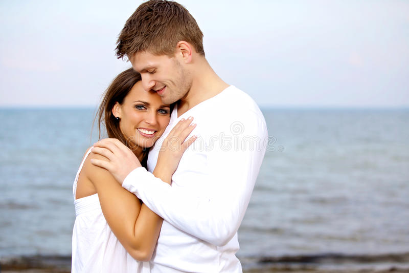 Het Geknuffel van het paar bij het Strand dat Gelukkig kijkt stock foto