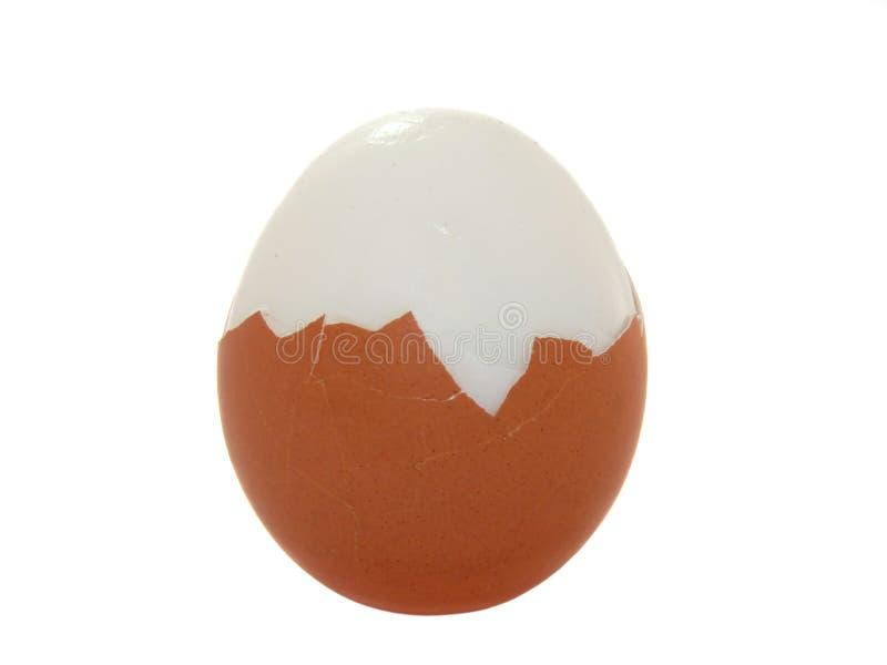 Het gekookte ei wordt half ontruimd, stock afbeeldingen