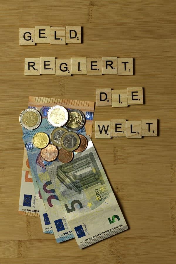 Het geld beslist de wereld, castreert het woord in het Duits regiert matrijzenrand royalty-vrije stock foto's