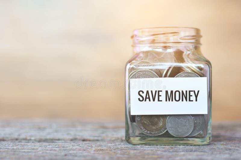Het geld in een glaskruik met ` bewaart geld` woord stock afbeeldingen