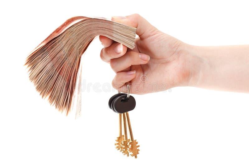 Het geld en het huissleutels van het contante geld ter beschikking royalty-vrije stock foto