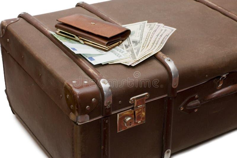 Het geld legt op een oude koffer stock afbeeldingen