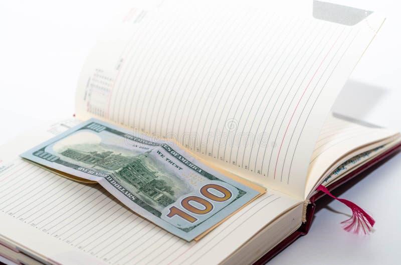 Het geld is op een open notitieboekje stock fotografie