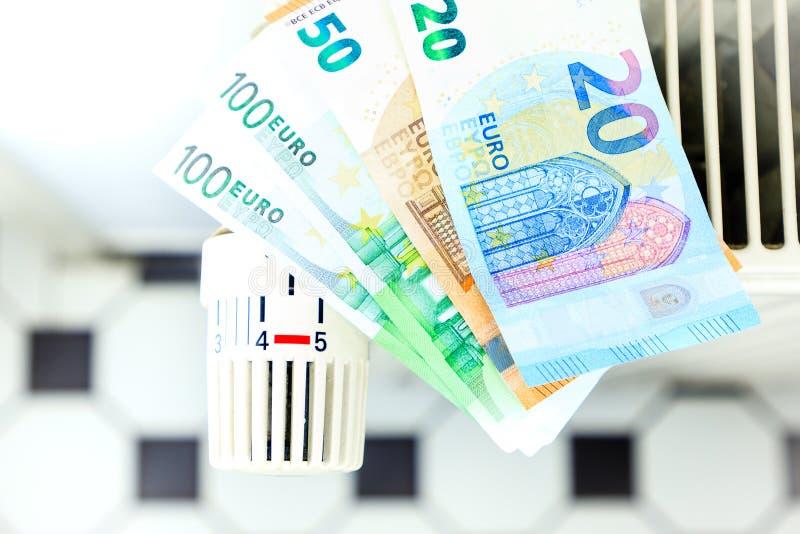 Het geld op een radiator symboliseert de dure verwarmingskostennen royalty-vrije stock foto