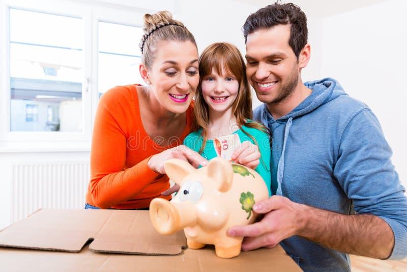 Het geld van de familiebesparing door huis te bewegen royalty-vrije stock fotografie