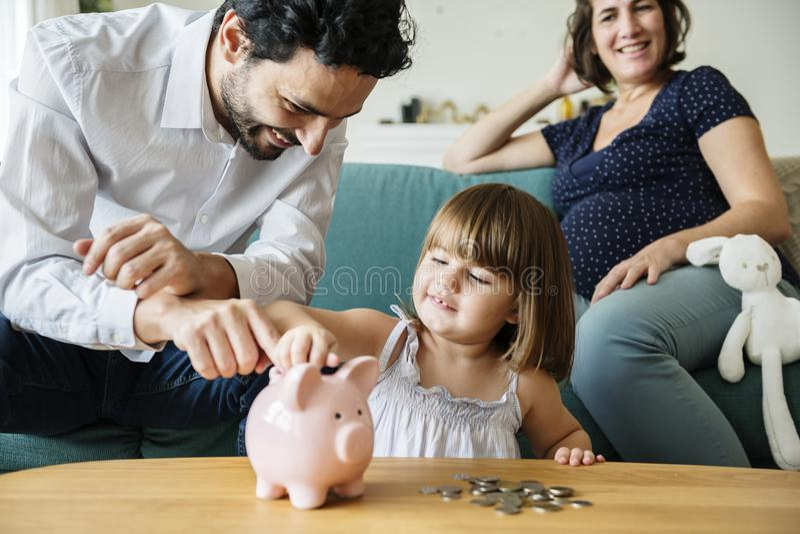 Het geld van de familiebesparing in spaarvarken stock afbeelding