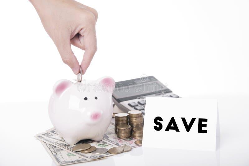 Het geld van de handbesparing in spaarvarken voor bericht spaart royalty-vrije stock afbeeldingen