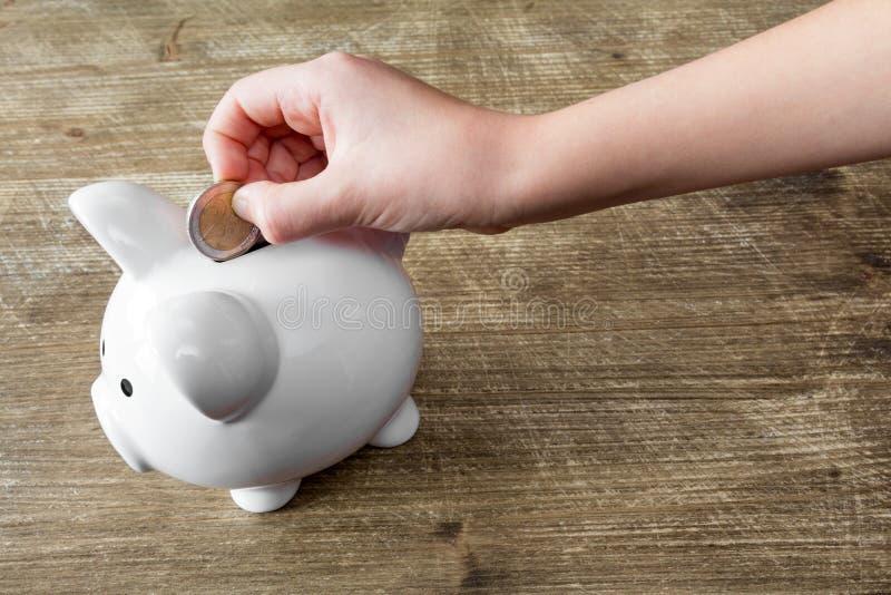 Het geld van de kindbesparing in spaarvarken stock afbeeldingen