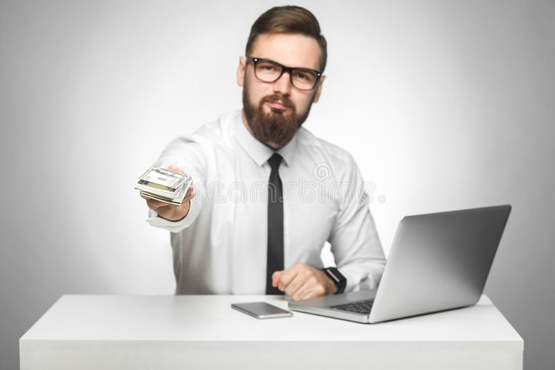 Het geld is van u! Het portret van knappe richman gebaarde jonge grote werkgever in wit overhemd en de avondkleding zitten in bur royalty-vrije stock afbeelding