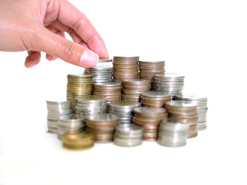 Het geldconcept van de besparing Vrouwenhand gezette muntstukken aan stapel muntstukken Besparingen, Financiën, het Concept van d royalty-vrije stock afbeelding