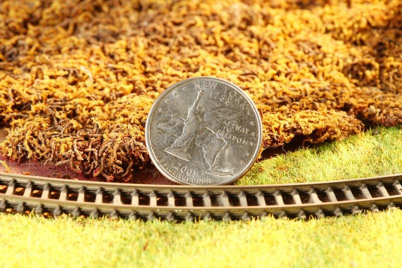 Het geldmuntstuk zette op de miniatuur modelspoorweg modelscène stock foto's
