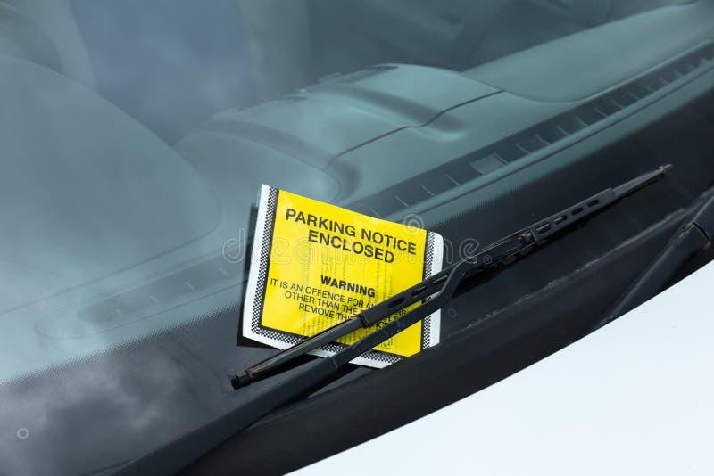 Het gele die kaartje van de parkerenhandhaving aan autovoorruit wordt geplakt stock afbeeldingen