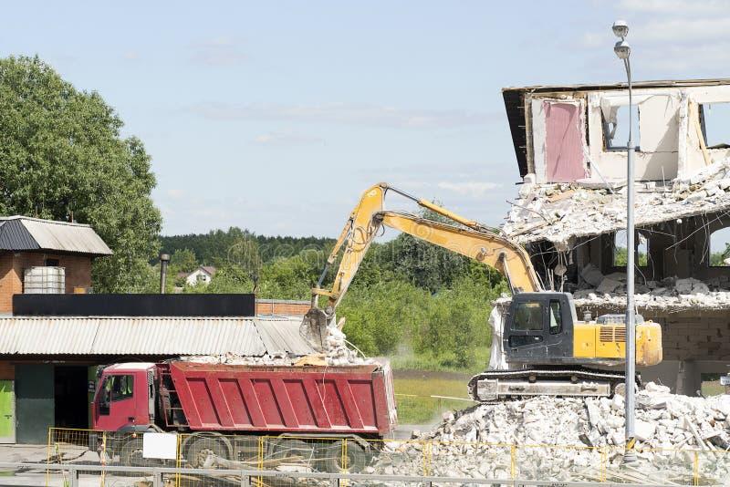 Het gele graafwerktuig laadt bouwpuin in de vrachtwagen De techniek vernietigt het gebouw, is montage, beton en stenen royalty-vrije stock foto's