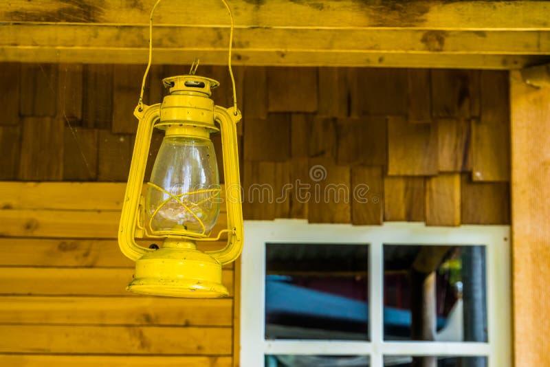 Het gele lantaarn hangen op het dak van een plattelandshuisje, basiskampverlichting stock afbeeldingen