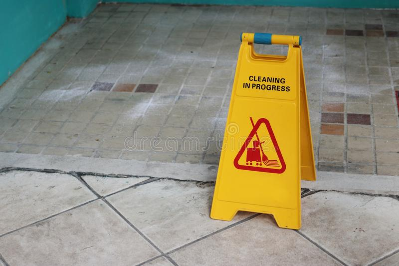 Het gele teken van de voorzichtigheids schoonmakende vooruitgang op de vloer in openlucht stock afbeeldingen