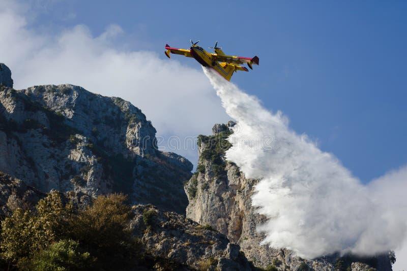 Het gele vliegtuig van de brandvechter laat vallen al water stock afbeelding
