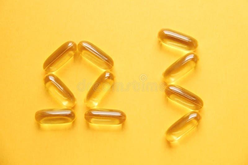 Het gele voedingshoogtepunt van supplementpillen van Omega 3 vetzuren stock foto