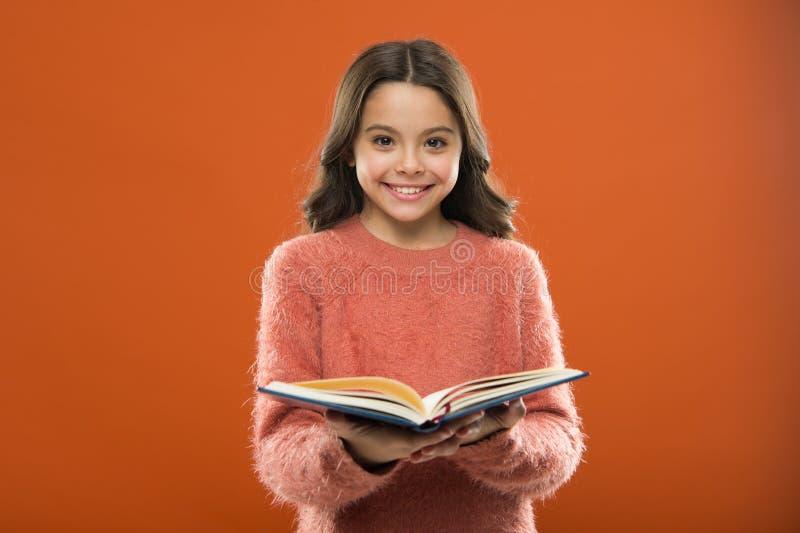 Het gelezen verhaal van de meisjesgreep boek over oranje achtergrond Het kind geniet van lezend boek Boekhandelconcept Prachtige  stock afbeeldingen