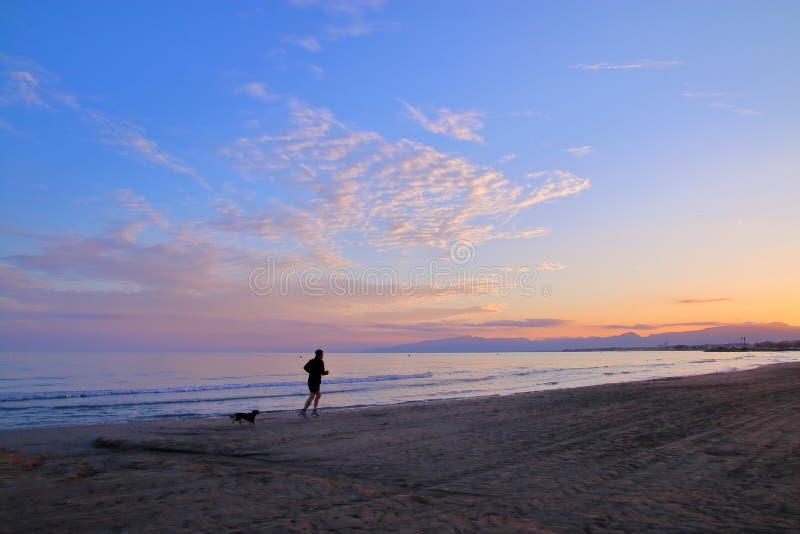 Het gelijk maken van jog langs het strand stock afbeeldingen