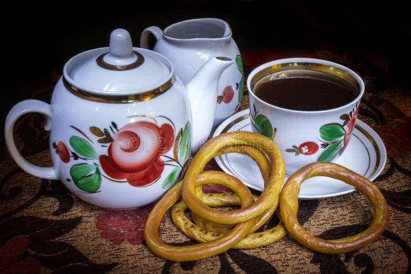 Het gelijk maken van zwarte thee met koekjes royalty-vrije stock afbeelding