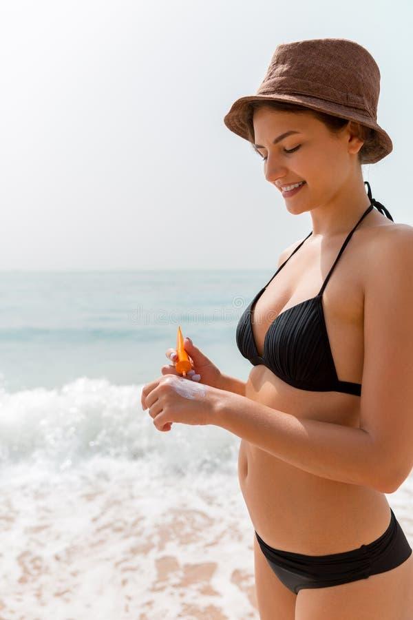 Het gelooide meisje gebruikt zonnescherm op haar hand bij het strand stock foto's