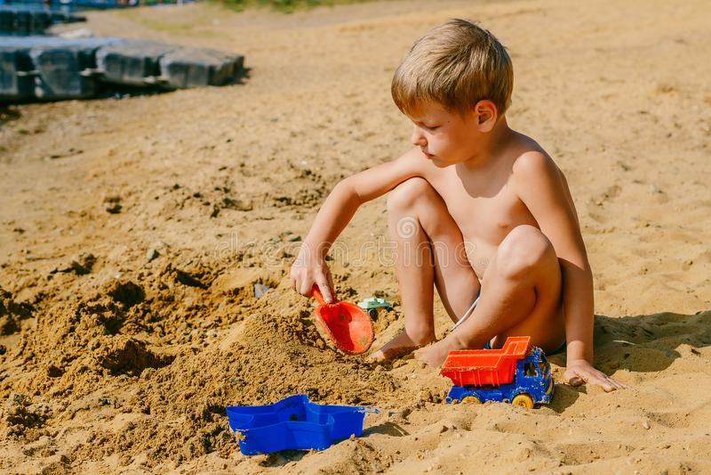 Het gelooide vijf-jaar-oude jongen spelen in het zand op het strand stock fotografie