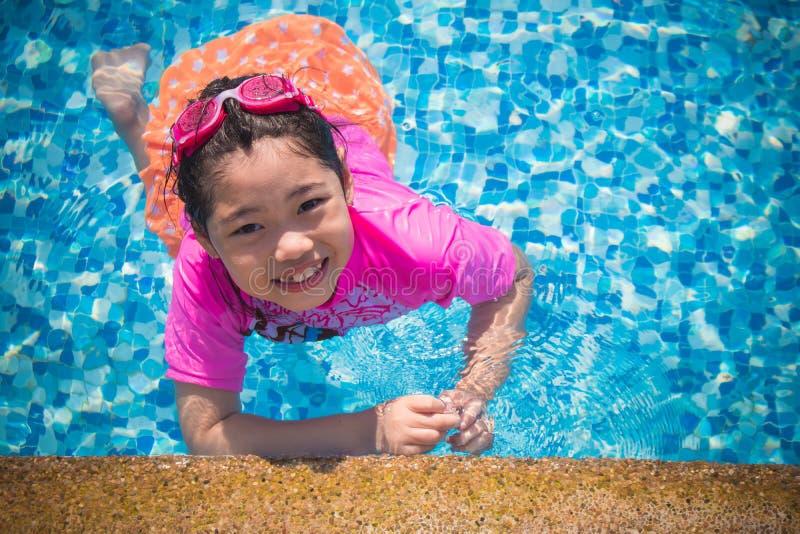 Het geluk en het Glimlachende Aziatische leuke meisje hebben grappig voelen en genieten van in zwembad stock afbeelding