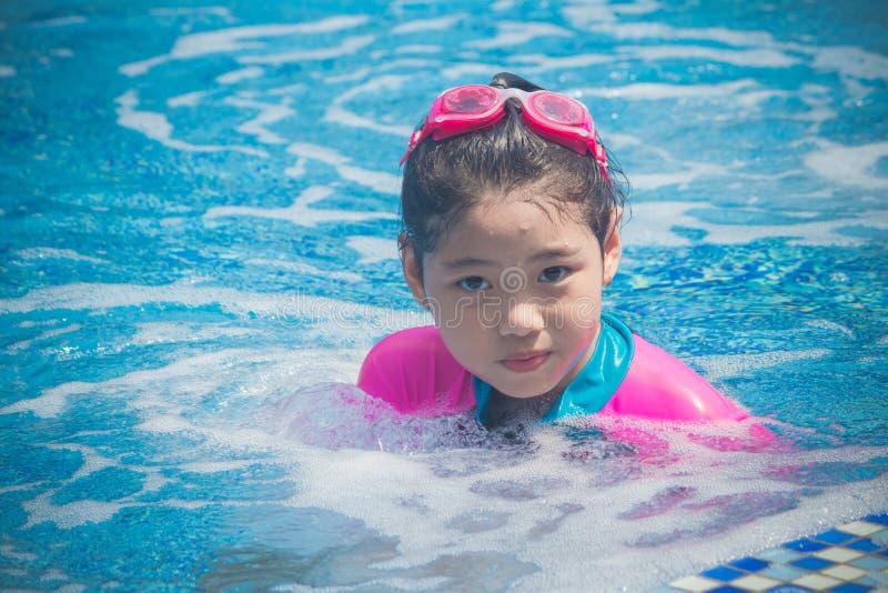 Het geluk en het Glimlachende Aziatische leuke meisje hebben grappig voelen en genieten van in zwembad royalty-vrije stock afbeelding