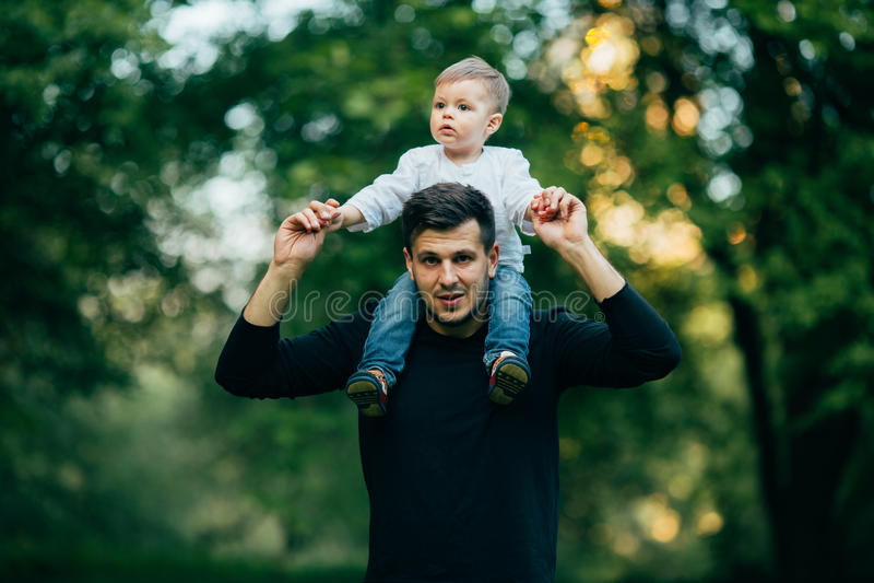 Het gelukkig weinig jongen overhandigt uitrekken zich uit terwijl zijn vader die hem vervoeren op schouders royalty-vrije stock afbeeldingen